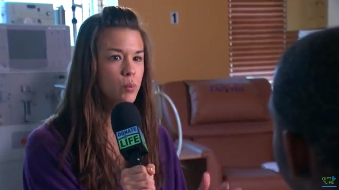 Nikki interviewing teen, holding microphone