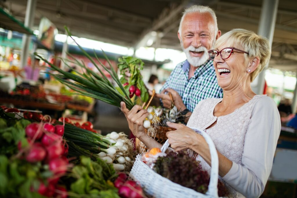 Smiling senior couple holding basket with vegetables at the market