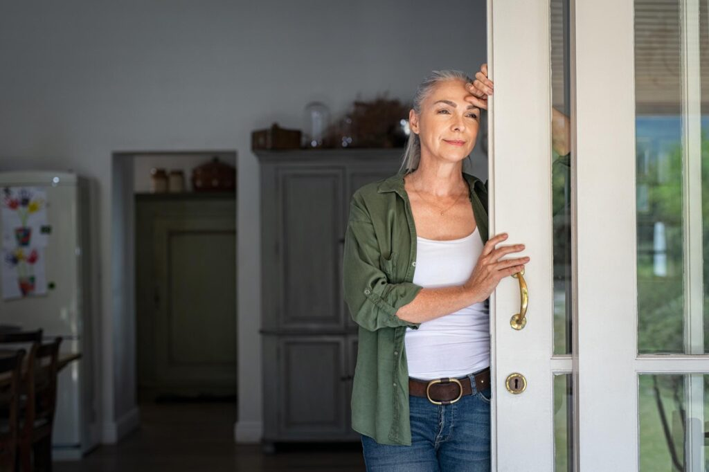Mature woman thinking at home entrance
