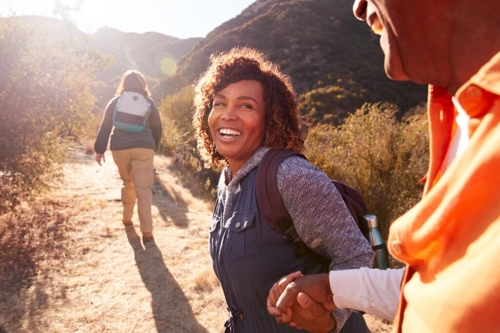 Woman Helping Man On Trail As Group Of Senior Friends Go Hiking In Countryside Together