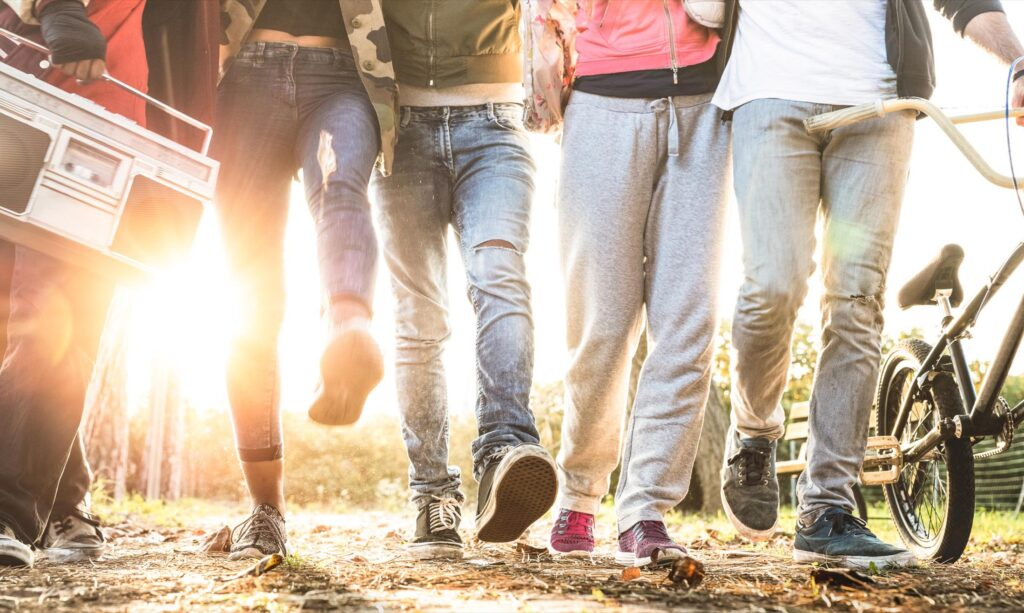Friends walking in city park with backlight and sunflare halo - Millenial friendship concept and multiracial young people on alternative fashion having fun together - Leg view with soft blurred motion