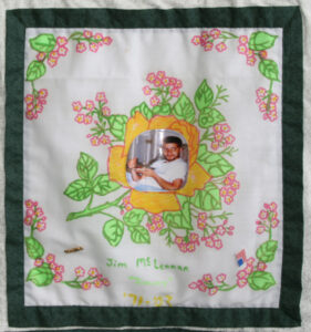 Jim McLennan, his photo fixed on a floral embroidered quilt square