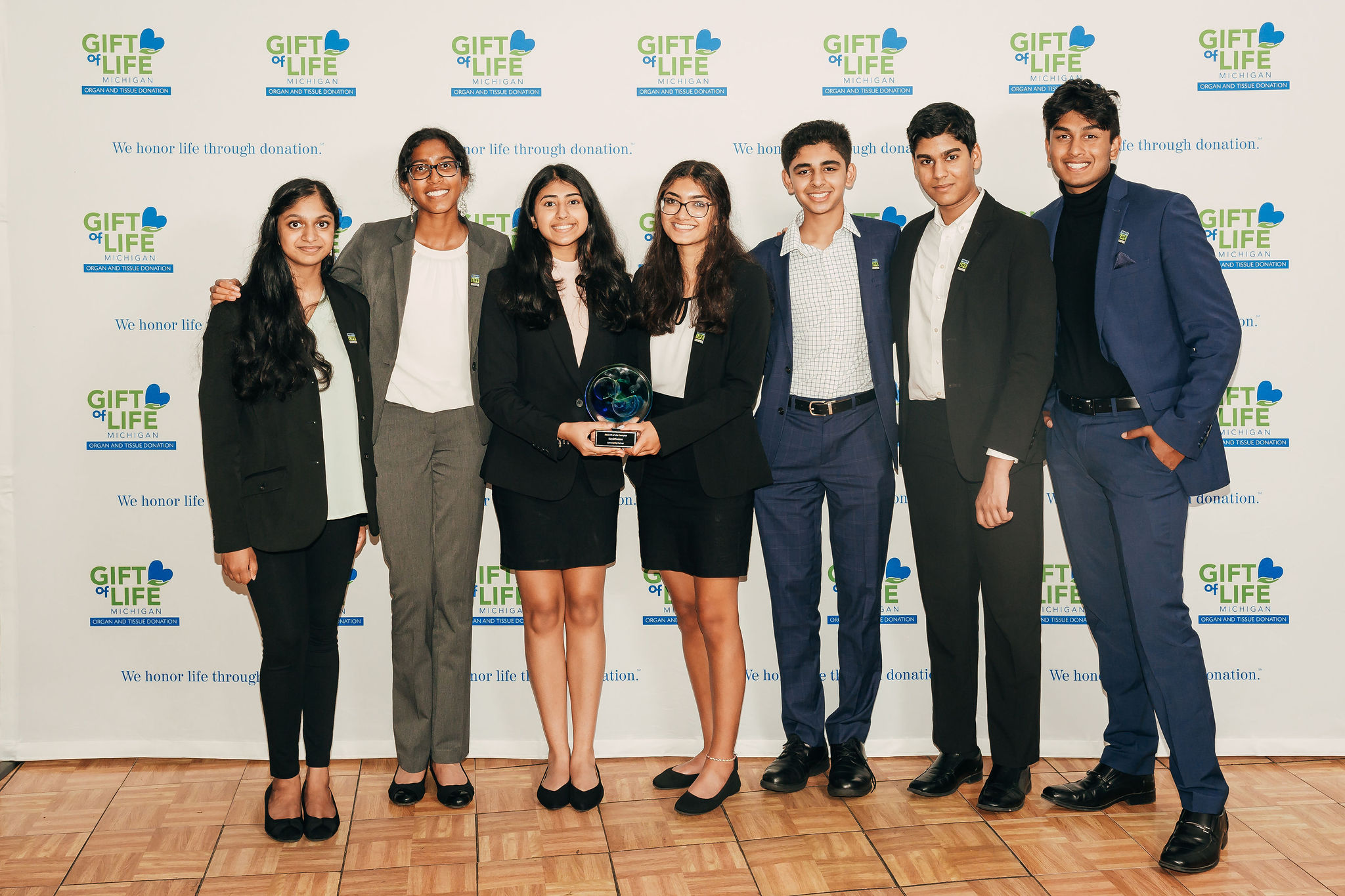 High school students in business attire holding an award