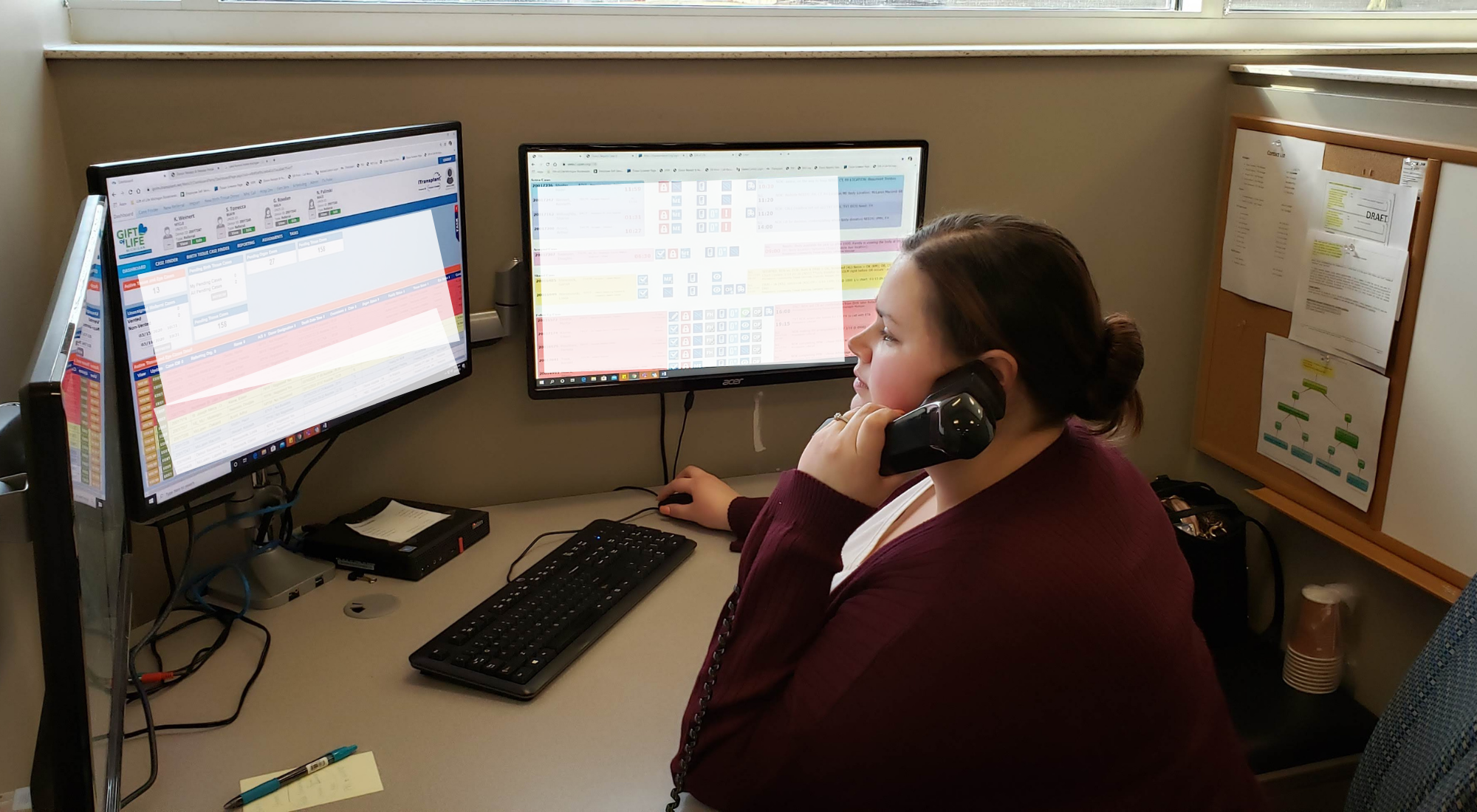 Woman in call center on phone, in front of computer