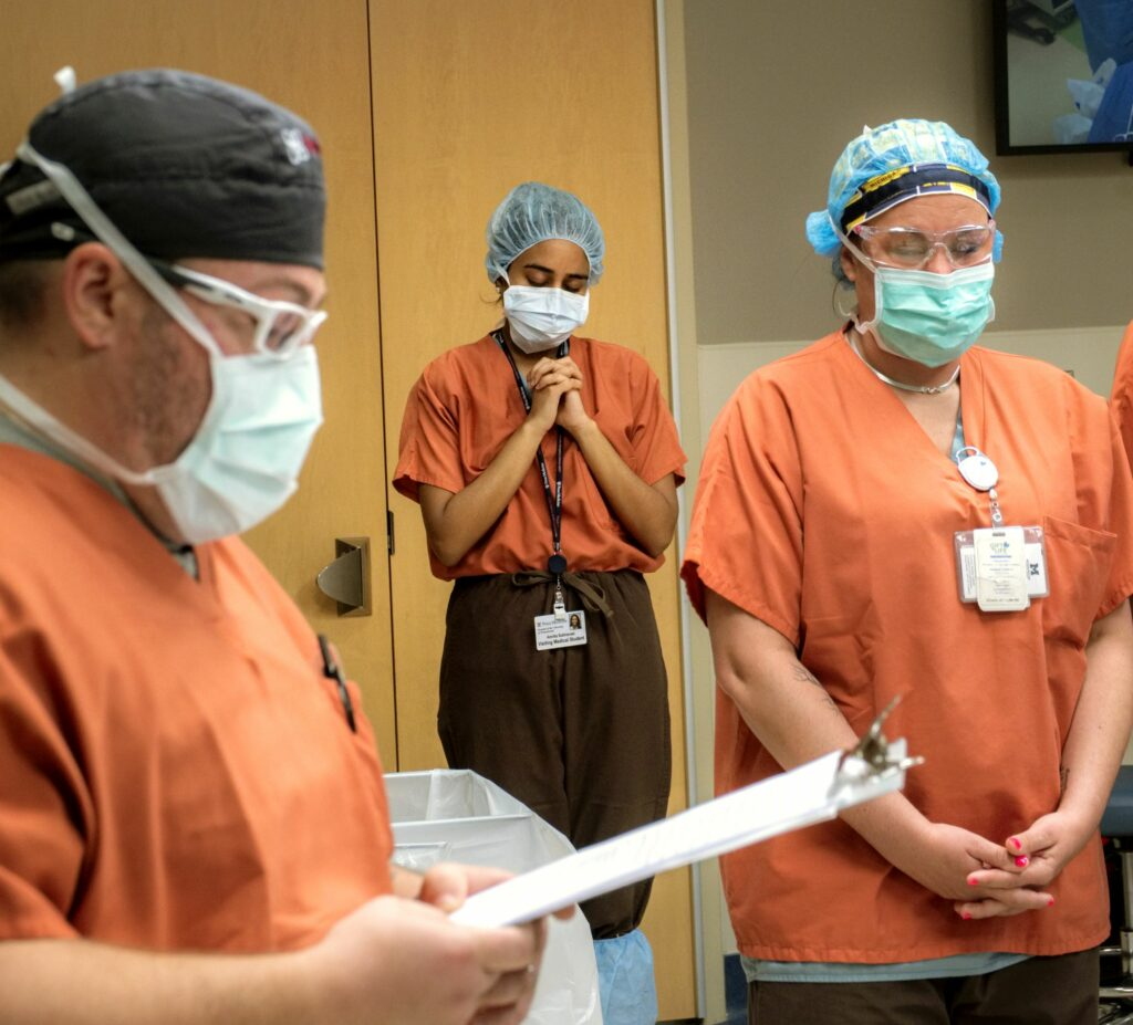 Three people in scrubs with heads bowed during pre-surgery moment of silence