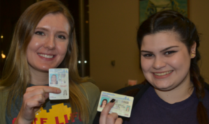 Two young women holding up driver's license