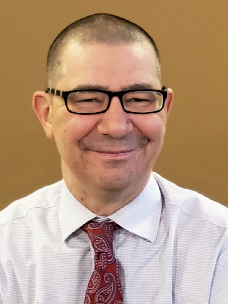 Man in glasses smiling at the camera